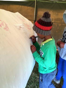 Children writing on mascot Lenny. Having their say against rhino poaching.